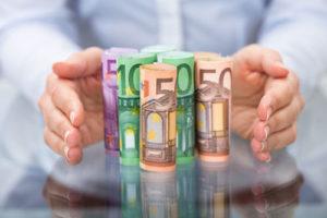 Ein hält schützend seine Hände um ein paar aufgestellte Rollen aus Geldscheinen