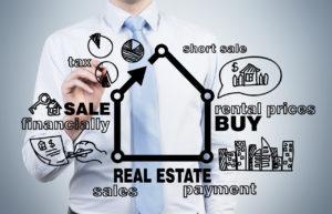 Ein Mann mit Krawatte zeichnet auf eine Glasscheibe Symbole rund um das Investment in Immobilien