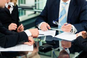 Vier Menschen im Business Outfit diskutieren über Details eines Vertrages, der auf dem Tisch liegt