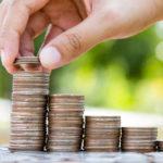 Eine Hand nimmt Münzen von nach rechts kleiner werdenden Münzstapeln