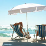 Ein Paar liegt entspannt in Liegestühlen am sonnigen Strand