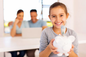 Ein Mädchen im Vordergrund hält ein Sparschein, im Hintergrund nutzen die Eltern einen Laptop