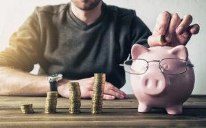 Ein junger Mann füttert ein Sparschwein mit Brille, neben dem ansteigende Münzstapel stehen