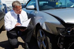 Ein Mann mit Klemmbrett begutachtet einen Autoschaden