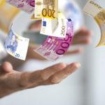 Offene Hand wirft verschiedene Euro Geldscheine in die Luft