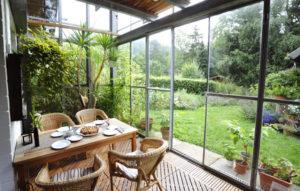 Ein Wintergarten mit Blick in den offenen Garten mit Hecke am Grundstücksende