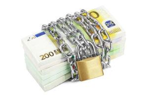 Eine Kette mit Vorhängeschloss umspannt mehrere Bündel mit Geldscheinen