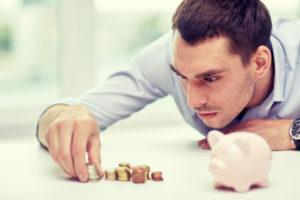 Ein junger Mann stapelt die Münzen neben seinem Sparschein