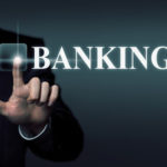 Zeigefinger eines Mannes berührt einen durchsichtigen Touochscreen auf dem das Wort Banking steht