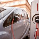 Graues Elektroauto wird an der Zapfsäule aufgeladen