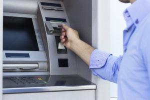Ein Mann zieht Geld am Geldautomat