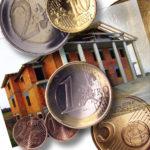 Ein paar Euro-Münzen vor einem halb fertig gestellten Neubau-Haus