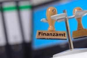 Ein Stempel mit der Aufschrift Finanzamt hängt in einem Ständer für Stempel