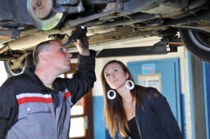 Eine junge Frauund ein Ingenieur prüfen den Unterboden eines Autos