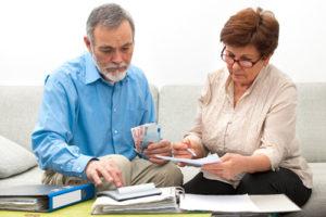 Ein älteres Paar wälzt Akten, nutzt einen Taschenrechner und er hält ein paar Euroscheine in der Hand