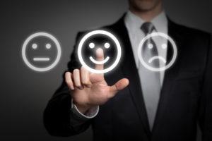 Ein Mann berücht das mittlere von drei Smileys, das lächelt