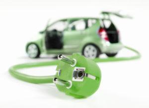 Ein grünes Stromkabel an dessen Ende ein grün lackiertes Auto hängt