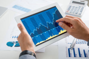 Ein Mann hält einen Tablet Computer der den positiven Chartverlauf eines Wertpapiers zeigt