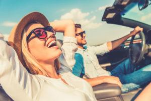 Ein junges Paar ist froh und entspannt im offenen Cabrio unterwegs