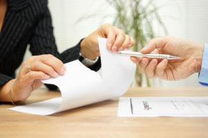 Ein Mann bietet einen Kugelschreiber zur Unterschrift an, doch die Frau zerreißt den Vertrag