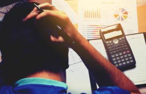 Ein Mann fasst sich beim Kalkulieren diverser Zahlen und Daten an den Kopf