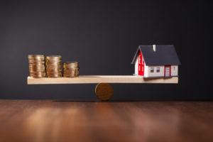 Eine Spielzeugwippe, auf der sich Münzen und ein Spielzeughaus gegenüber stehen