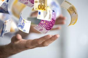 Eine offene Hand wirft viele Euro Scheine in die Luft