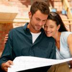 Junges fröhliches Paar steht vor einer Baustelle und studiert einen Bauplan