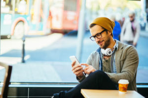 Ein junger Mann sitzt bei einem Kaffe, hat Kopfhörer um den Hals gelegt und tippt auf seinem Handy