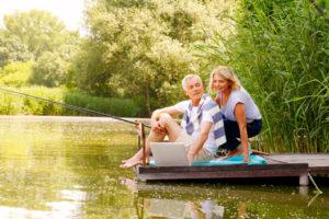 Ein Paar mittleren Alters sitzt auf einem Holzsteg und hat eine Angel und einen Laptop dabei