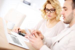 Ein junges Paar rechnet diverse Angebote mit Taschenrechner und Laptop nach