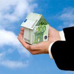Hände halten gefaltetes Häuschen aus 100 Euro Scheinen