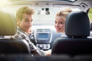 Ein junges fröhliches Paar sitzt vorn im Auto und dreht sich in der Mitte nach hinten um