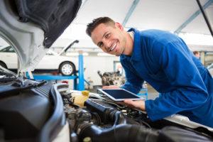 Ein junger Ingenieur mit Tablet Computer beugt sich über einen Automotor
