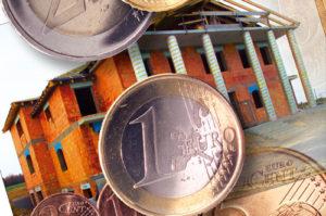 Einige Euromünzen auf dem Bild eines Rohbaus