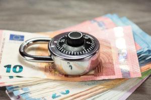 Ein Vorhängeschloss liegt auf einem Stapel Geldscheine