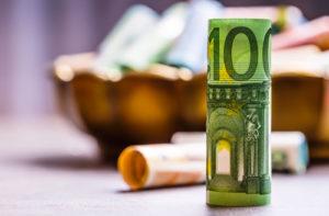 Ein aufgerollter hundert Euro Schein steht vor einer kleinen Holzschale mit mehreren gerollten Geldscheinen