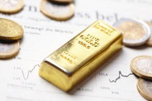Ein kleiner Goldbarren liegt auf einem Blatt mit Daten und Kurse neben einigen Münzen