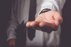 Ein Mann mit Krawatte und Dokumententasche hält die Hand auf