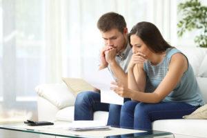 Ein junges Paar sitzt auf einer Couch und grübelt über einen Vertrag