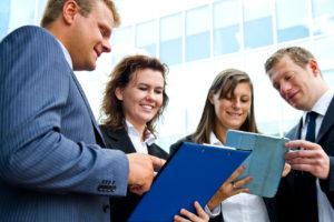 Vier Personen im Business Outfit unterhalten sich und nutzen zwei Tablet-Computer