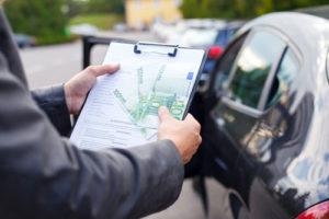Ein Mann mitt Klemmbrett, Checkliste und drei hundert Euro Scheinen checkt ein Auto