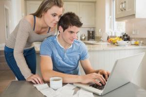 Ein Junges Paar bezahlt Rechnungen am Computer