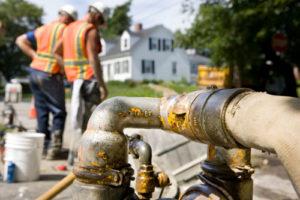 Zwei Bauarbeiter pumpen mit großen Schläuchen Wasser ab