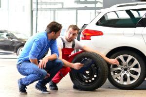 Ein Mechaniker erklärt einem Kunden etwas am Reifen seines Wagens