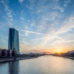 Das Gebäude der EZB vor blauem Himmel und aufgehender Sonne