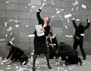 Personen im Business Outfit versuchen herumwirbelndes Geld einzufangen
