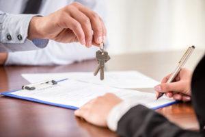 Ein Mann unterschreibt einen Vertrag während ein anderer ihm zwei Hausschlüssel reicht