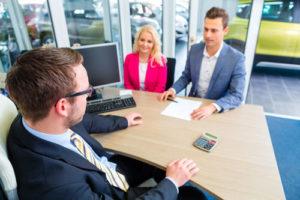 Ein Paar sitzt mit einem Autohändler am Tisch und diskutiert die Verträge zum Autokauf