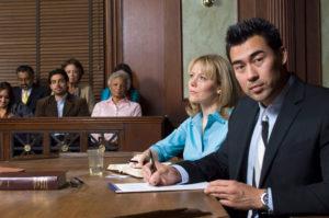 Ein Anwalt und eine Frau sitzen am Tisch vor einem Gericht und haben Unterlagen vor sich